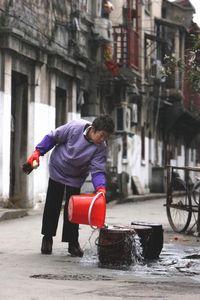 4旧上海后街小巷,旧上海的象征 馬桶(便壺)を洗浄する主婦