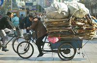 15上海街頭的民工(流動工人)騎着装満廃物的三輪車